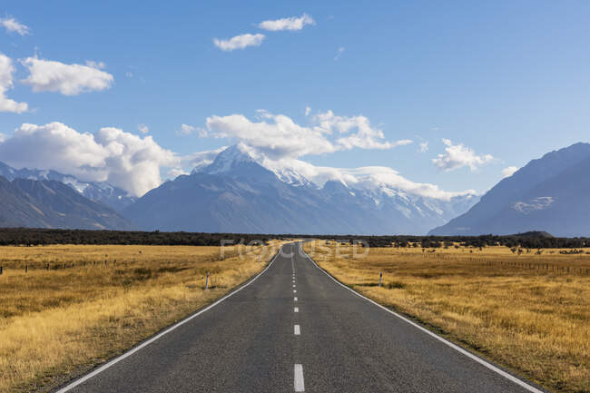 Nueva Zelanda, Oceanía, Isla Sur, Canterbury, Ben Ohau, Alpes del Sur (Alpes de Nueva Zelanda), Parque Nacional Mount Cook, Mount Cook Road y Aoraki / Mount Cook, Camino vacío en el paisaje de montaña - foto de stock