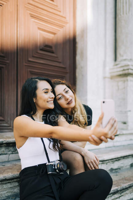 Retrato de dos freinds sentados en escaleras tomando selfie con smartphone, Lisboa, Portugal - foto de stock