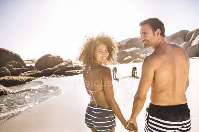 Coppia felice sulla spiaggia con bambini sullo sfondo — Foto stock