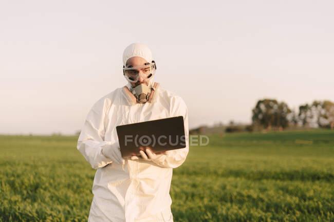 Hombre con traje de protección y máscara en el campo usando el ordenador portátil - foto de stock