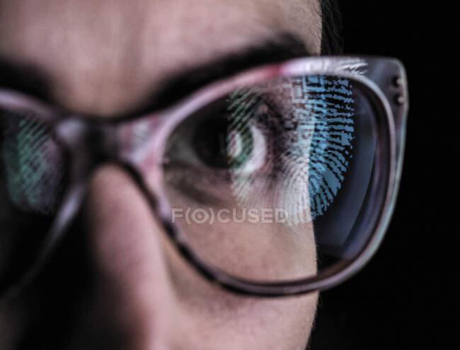 Жінка з відбиттям пальця на окулярах, щоб представляти ідентичність і доступ — стокове фото