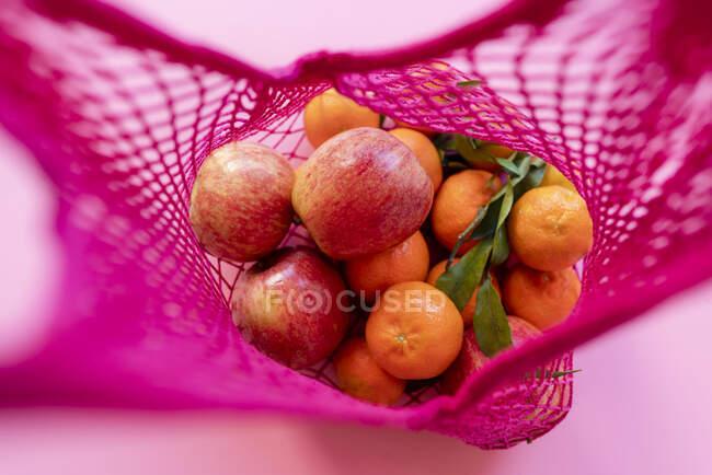 Clementinas y manzanas frescas en bolsa de malla reutilizable ecológica - foto de stock