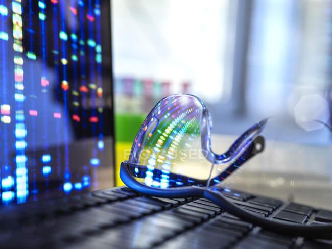 Результати профілю ДНК відображають захисні окуляри лежачі на клавіатурі ноутбука — стокове фото