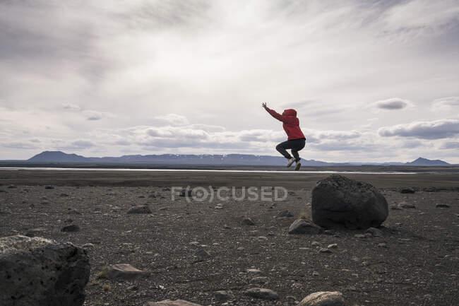 Молода жінка стрибає з скелі в вулканічному нагір