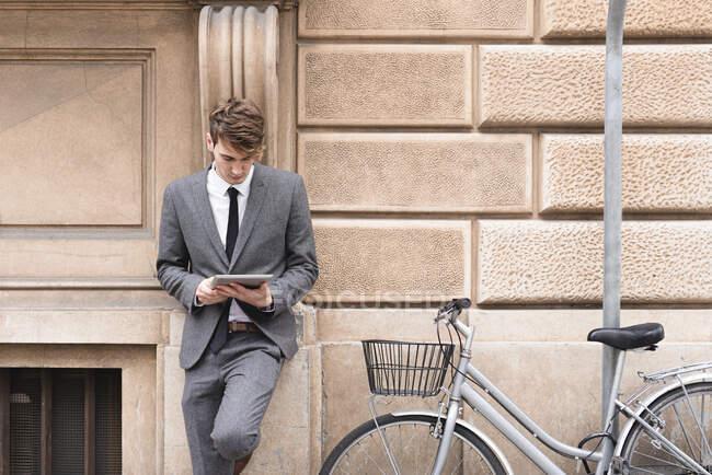 Jeune homme d'affaires penché sur la façade regardant tablette numérique — Photo de stock