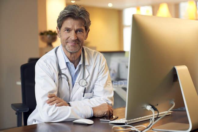 Retrato del médico confiado en el escritorio en su práctica médica - foto de stock