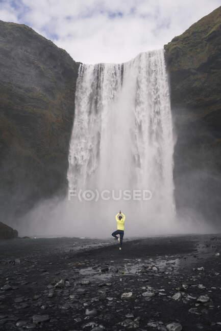 Молода жінка практикує йогу перед водоспадами Скогафоса (Ісландія). — стокове фото