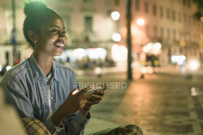 Портрет счастливой молодой женщины, использующей смартфон в городе ночью, Лиссабон, Португалия — стоковое фото