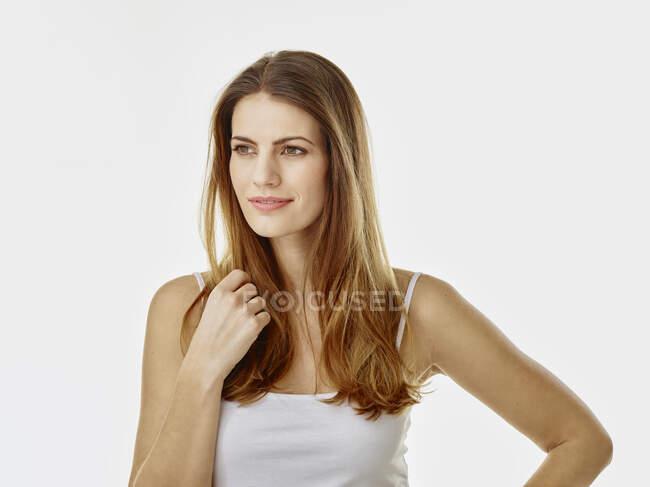 Porträt einer lächelnden Frau mit langen Haaren vor weißem Hintergrund — Stockfoto