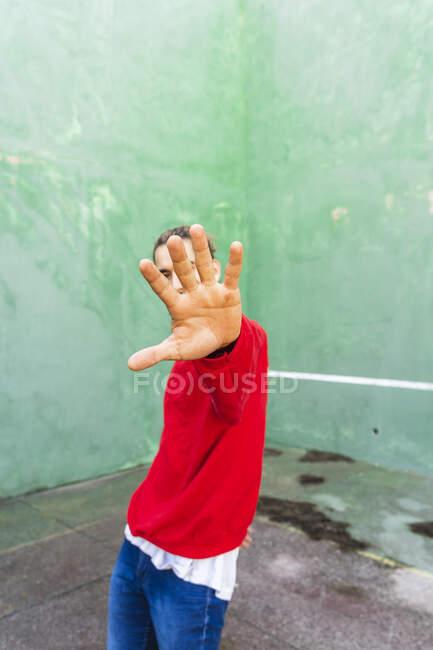 Giovane uomo che indossa felpa rossa alzando la mano — Foto stock