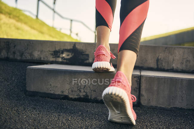 Legs of woman running in the city, rear view — Stock Photo
