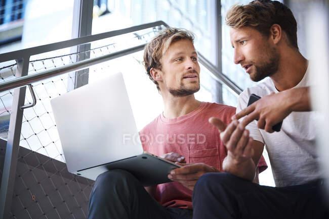 Двоє молодих чоловіків, які сидять на сходах за допомогою ноутбука. — стокове фото