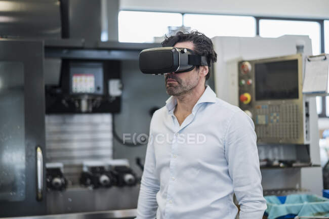 Businessman wearing VR glasses in a factory — Stock Photo