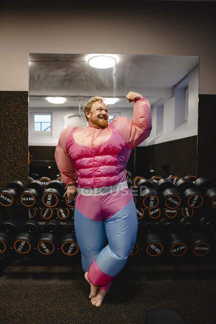 Orgulloso hombre con traje de culturista rosa flexionando sus músculos - foto de stock