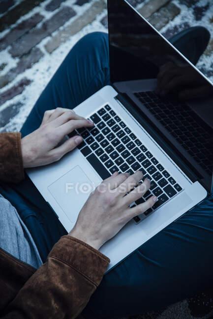 Підліток користується ноутбуком і сидить на кам