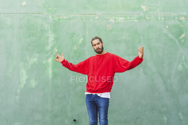 Portrait of angry young man wearing red sweatshirt in front of green wall — Stock Photo