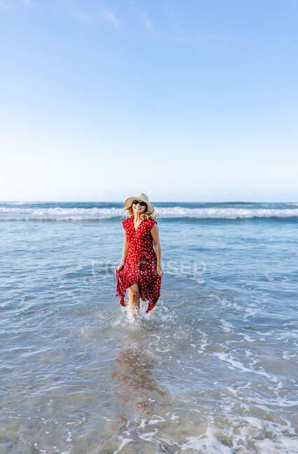 Donna bionda vestita di rosso e cappello in spiaggia, che corre in acqua — Foto stock