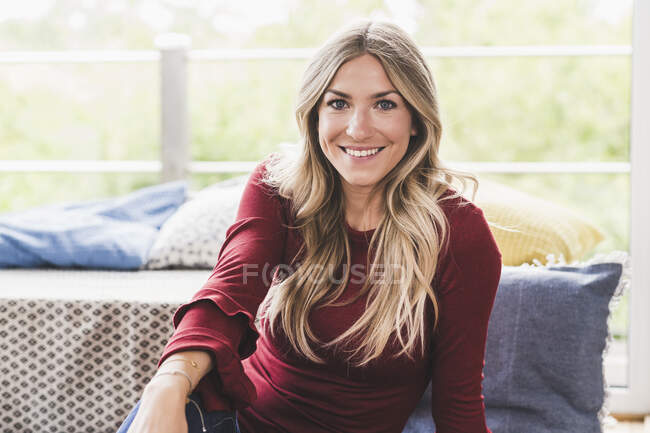Портрет улыбающейся блондинки, отдыхающей дома — стоковое фото