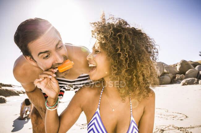 Donna che condivide ghiacciolo con l'uomo sulla spiaggia — Foto stock