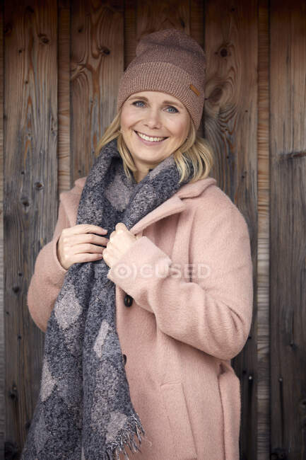 Portrait of smiling woman in winter clothes at wooden wall — Stock Photo