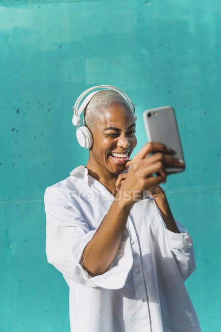 Hermosa mujer de pie frente a la pared verde azulado, escuchando música, tomando selfies - foto de stock