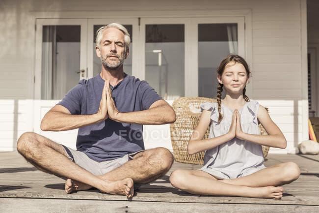 Отец и дочь сидят на террасе под солнцем и занимаются йогой. — стоковое фото