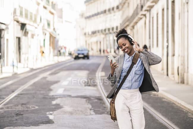 Щаслива молода жінка з навушниками та мобільним телефоном у місті Лісабон (Португалія). — стокове фото