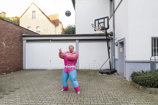 Retrato de un hombre con baloncesto vistiendo traje de culturista rosa - foto de stock