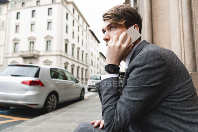Young businessman with smartwatch on the phone in the city — Stock Photo
