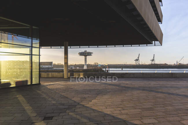 Germany, Hamburg, Canopy over pavement in HafenCity at sunrise with Lighthouse Zero in background — Stock Photo