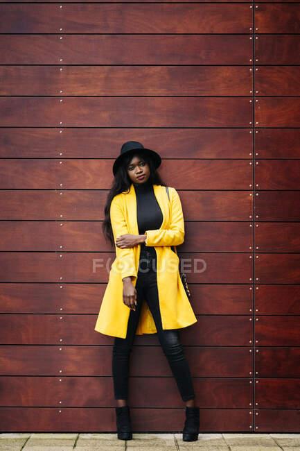 Retrato de mulher jovem na moda em pé em uma parede de madeira — Fotografia de Stock