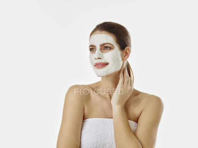 Retrato de mulher sorridente com máscara de beleza na frente do fundo branco — Fotografia de Stock
