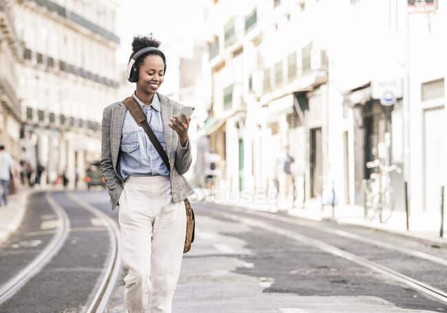 Jovem sorridente com auscultadores e telemóvel em movimento na cidade, Lisboa, Portugal — Fotografia de Stock