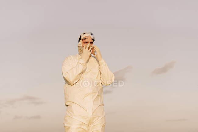 Hombre con traje protector y máscara en el campo - foto de stock