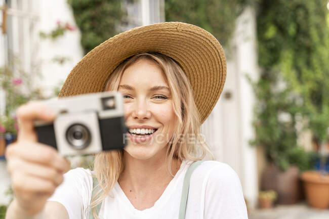 Retrato de mujer joven y feliz con cámara - foto de stock