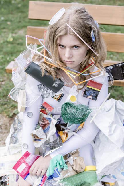 Adolescente vestito bianco con rifiuti di plastica, accanto a un — Foto stock