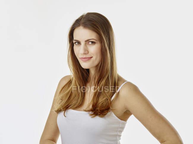 Ritratto di donna sorridente con i capelli lunghi sullo sfondo bianco — Foto stock