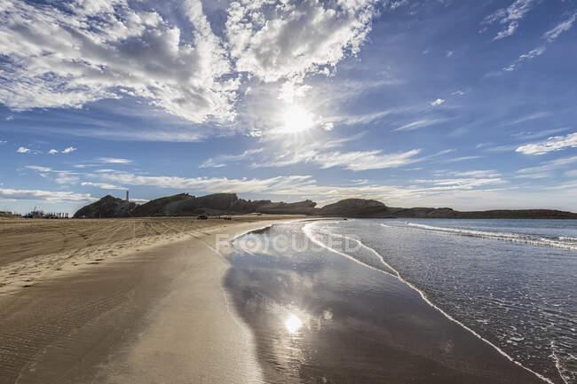 Nueva Zelanda, Región de Wellington, Castlepoint, Sol brillando sobre la playa costera de arena del Océano Pacífico - foto de stock