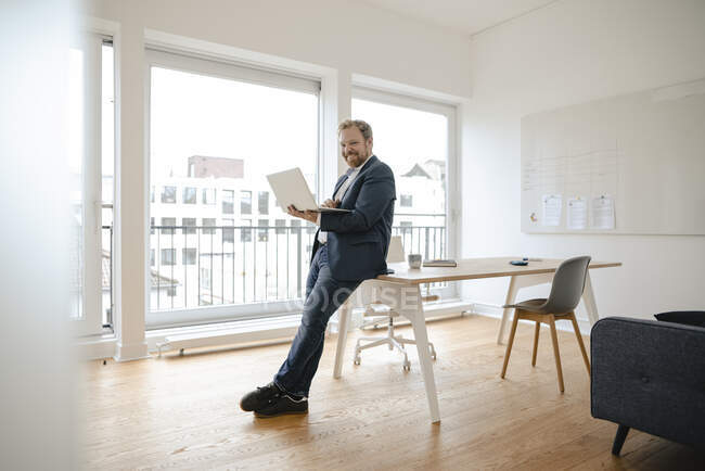 Smiling businessman using laptop in office — Stock Photo