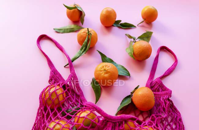 Estudio de clementinas maduras y bolsa de malla reutilizable ecológica - foto de stock