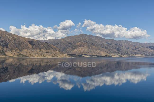 Нова Зеландія, Квінстаун-Лейкс район, Ванака, пагорби і блакитне літнє небо відбивають в озері Гавеа — стокове фото
