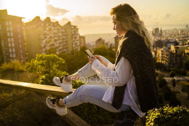 Mujer joven sentada en la barandilla sobre la ciudad usando el teléfono celular, Barcelona, España - foto de stock