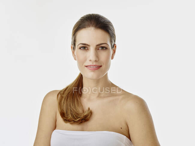 Portrait of smiling woman against white background — Stock Photo