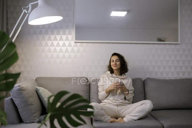Портрет улыбающейся женщины, отдыхающей с чашкой чая на диване дома — стоковое фото