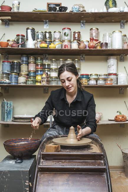 Женщина, работающая над заготовкой в керамике — стоковое фото