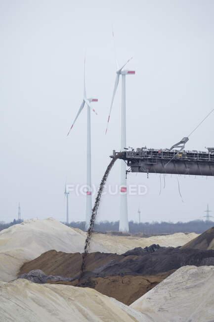 Allemagne, Rhénanie-du-Nord-Westphalie, Inden, Courroie transporteuse d'excavatrice à godets avec éoliennes en arrière-plan — Photo de stock