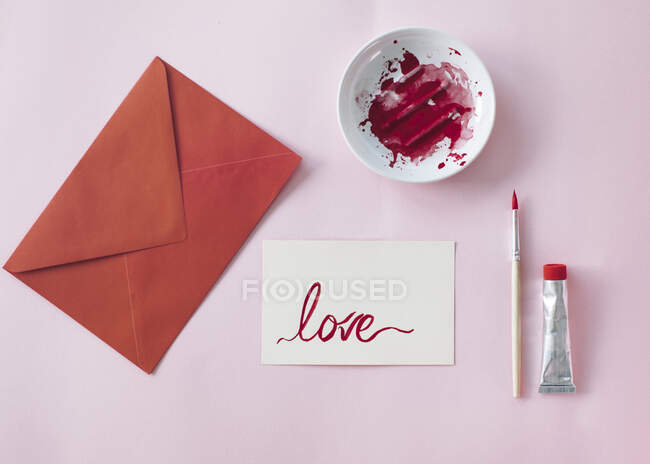Making a Valetine's day card, red envelope and card with love written on it — Stock Photo