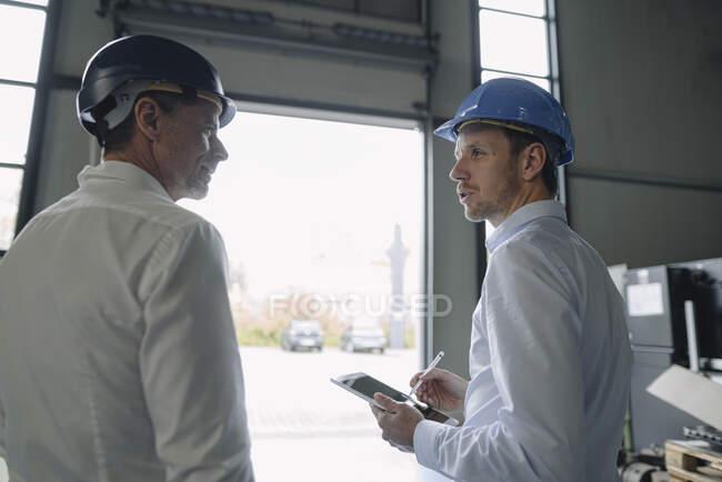 Двоє чоловіків у твердих капелюхах розмовляють на фабриці. — стокове фото