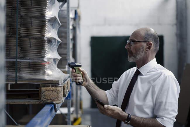 Hombre con smartphone y escáner en almacén de fábrica - foto de stock
