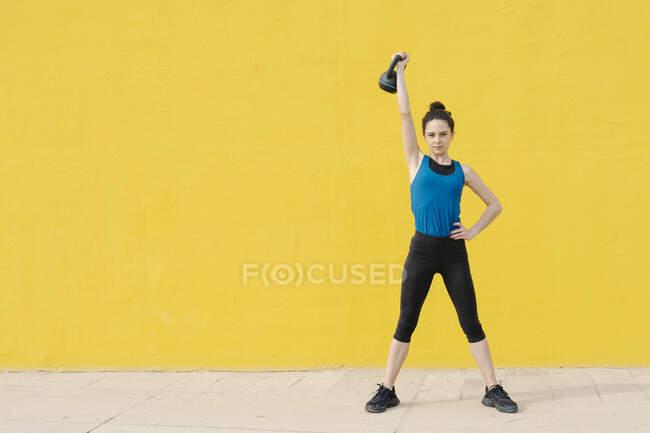 Молодая женщина тренируется с гантели перед желтой стеной — стоковое фото
